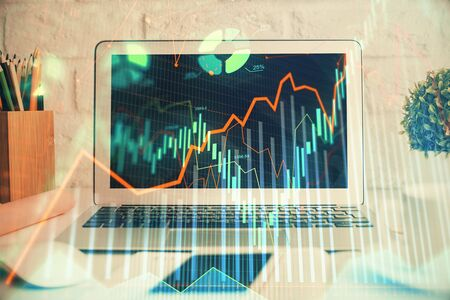 Stock market graph on background with desk and personal computer. Multi exposure. Concept of financial analysis.