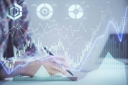 Manos de una mujer escribiendo información sobre el mercado de valores en el bloc de notas. Hologramas de gráficos de Forex en el frente. Concepto de investigación. Exposición doble
