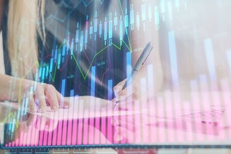 A woman hands writing information about stock market in notepad. Forex chart holograms in front. Concept of research. Double exposure Stockfoto
