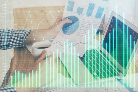 Double exposure of businessmans hands withcup of coffee with stock market graph background. Concept of research and trading. Zdjęcie Seryjne