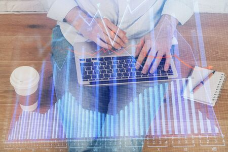 Double exposure of mans hands writing notes of stock market with forex graph background. Concept of research and trading. Zdjęcie Seryjne