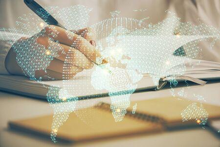 International business hologram over hands taking notes 写真素材
