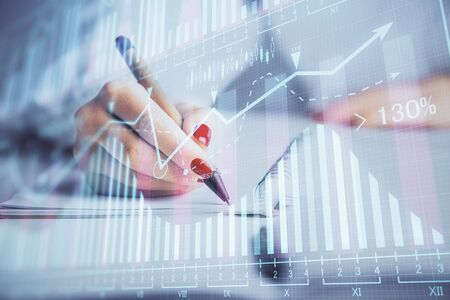 Double exposure of womans hands making notes with forex graph hologram.