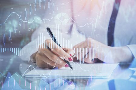 Double exposure of hands making notes with forex chart huds.