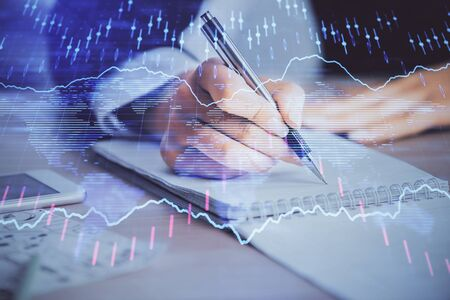 A woman hands writing information about stock market in notepad.