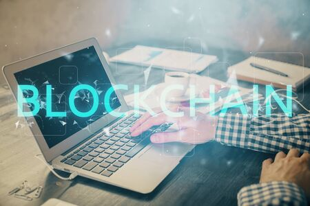 Blockchain theme hologram with man working on computer