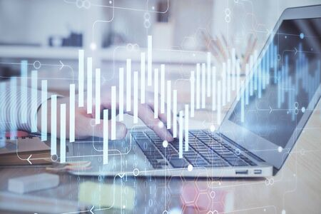 Double exposure of stock market graph with man working on laptop