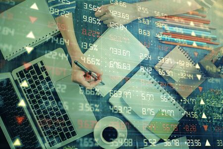 Financial chart drawn over hands taking notes background. Concept of research. Double exposure Stock Photo