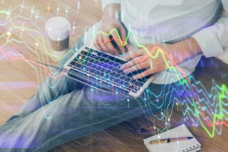 Forex graph with businessman working on computer in office on background. Concept of analysis. Double exposure. 写真素材