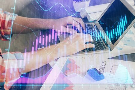 Double exposure of stock graph with businessman typing on computer in office Stock Photo