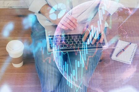 Double exposure of mans hands writing notes of stock market with forex graph background. Concept of research and trading. Stockfoto