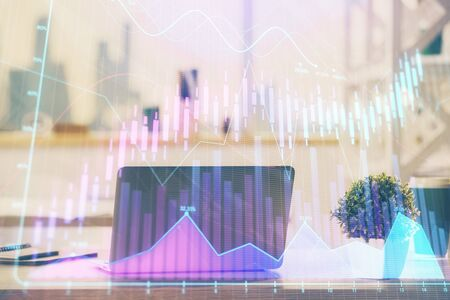 Stock market chart hologram drawn on personal computer 写真素材
