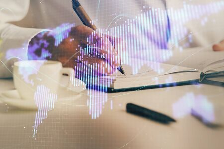 Double exposure of hands and notepad with business icons.