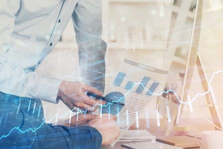 Double exposure of chart with businessman typing on computer in office on background. Concept of hard work.