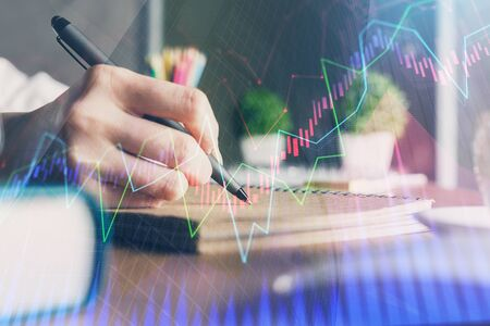 Financial forex charts displayed on womans hand taking notes background. Concept of research. Double exposure Stok Fotoğraf