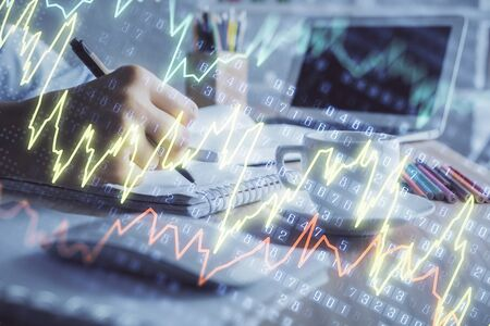 Financial chart drawn over hands taking notes background. Concept of research. Double exposure 写真素材