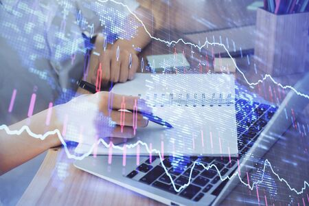 Financial charts displayed on womans hand taking notes background. Concept of research. Double exposure