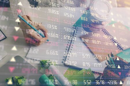 Financial forex graph displayed on hands taking notes background. Concept of research. Multi exposure Banque d'images - 129473390