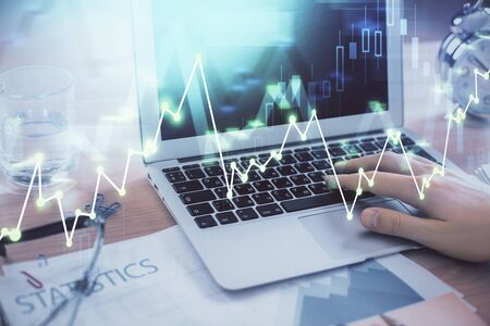 Multi exposure of market chart with man working on computer on background. Concept of financial analysis.