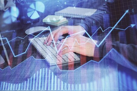 Stock graph with businessman typing on computer in office on background. Concept of analysis. Double exposure. Banque d'images - 129473504