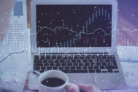 Financial chart drawing and table with computer on background. Double exposure. Concept of international markets.
