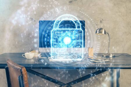 Double exposure of desktop with computer and lock icon hologram. Concept of data safety.