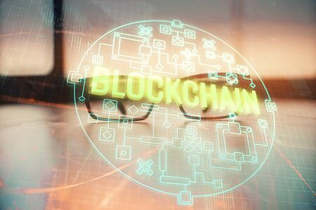 Crypto theme hologram with glasses on the table background. Concept of blockchain. Double exposure. Zdjęcie Seryjne