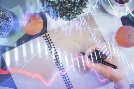Forex chart hologram on hand taking notes background. Concept of analysis. Double exposure Stock fotó