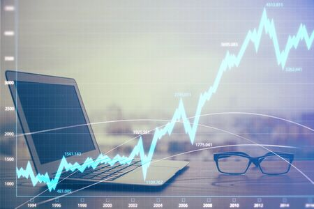 Stock market graph on background with desk and personal computer. Multi exposure. Concept of financial analysis. Stok Fotoğraf - 129829013