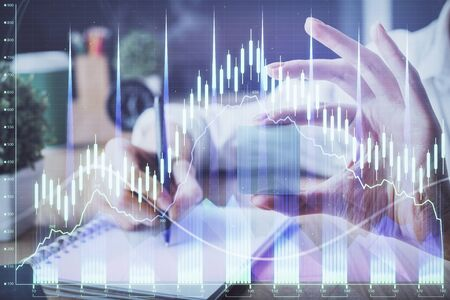 Forex chart displayed on woman's hand taking notes background. Concept of research. Multi exposure Stok Fotoğraf - 129829090