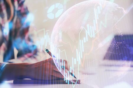 A woman hands writing information about stock market in notepad. Forex chart holograms in front. Concept of research. Double exposure Stock fotó