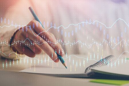 Financial forex graph displayed on hands taking notes background. Concept of research. Double exposure Stok Fotoğraf - 129829333