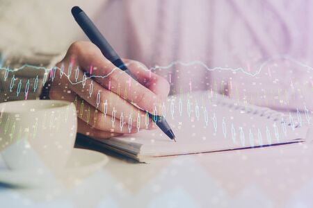 Forex chart displayed on woman's hand taking notes background. Concept of research. Double exposure Stok Fotoğraf - 129829499