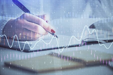 Multi exposure of womans hands making notes with forex graph hologram. Concept stock market analysis.