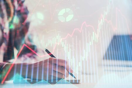 A woman hands writing information about stock market in notepad. Forex chart holograms in front. Concept of research. Double exposure Stock Photo