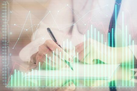 Double exposure of hands making notes with forex chart huds. Stock market concept. Stock Photo