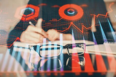 Forex chart hologram on hand taking notes background. Concept of analysis. Multi exposure Stock Photo