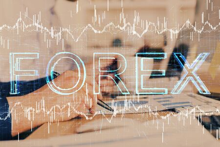 Double exposure of mans hands writing notes of stock market with forex graph. Banco de Imagens