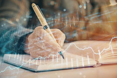 Multi exposure of womans hands making notes with forex graph hologram. Concept of technical analysis. Stock Photo