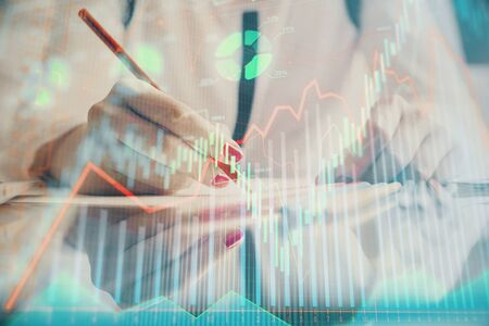 A woman hands writing information about stock market in notepad. Forex chart holograms in front. Concept of research. Stock Photo