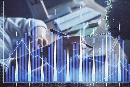 Financial forex charts displayed on womans hand taking notes background. Concept of research. Double exposure Stock Photo