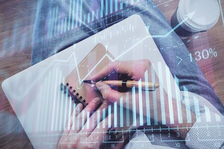 Double exposure of man doing notes of stock market with forex graph. Stok Fotoğraf - 131482267