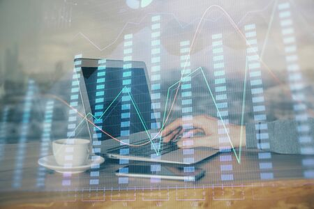 Double exposure of mans hands writing notes of stock market with forex graph background. Concept of research and trading. 版權商用圖片