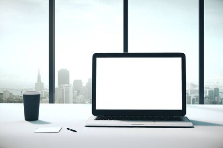 blank laptop with on white desk with coffee cup and bright city view. Mock up, 3D Rendering Reklamní fotografie