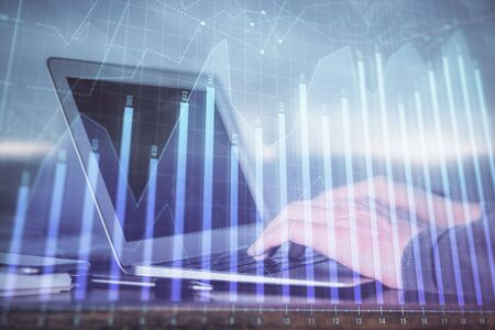 Double exposure of mans hands writing notes of stock market with forex graph background. Concept of research and trading.