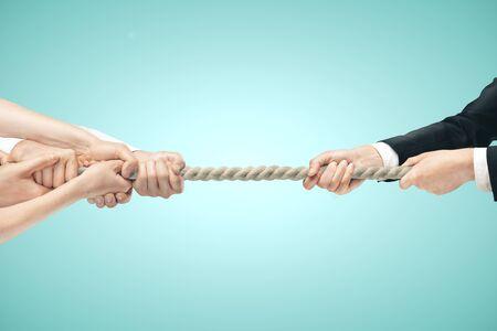 Hombre de negocios y varias manos durante tira y afloja sobre fondos azules. Concepto de competencia empresarial Foto de archivo