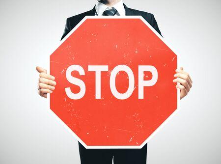Uomo d'affari che tiene in mano un segnale di stop. Concetto di motivazione aziendale. Avvicinamento Archivio Fotografico