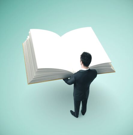 Small businessman in suit holding big book.  Business education concept