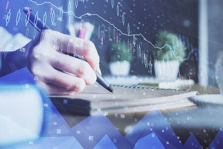 Financial forex charts displayed on womans hand taking notes background. Concept of research. Double exposure Zdjęcie Seryjne