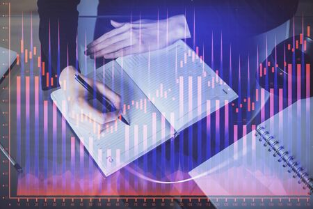 Forex chart hologram on hand taking notes background. Concept of analysis. Multi exposure Stok Fotoğraf
